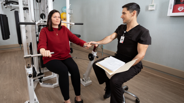 A physical therapist assists patient while using therapy machine.