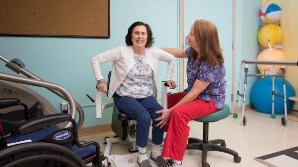 A physical therapist supports a patient while she lifts herself out of a therapy machine.