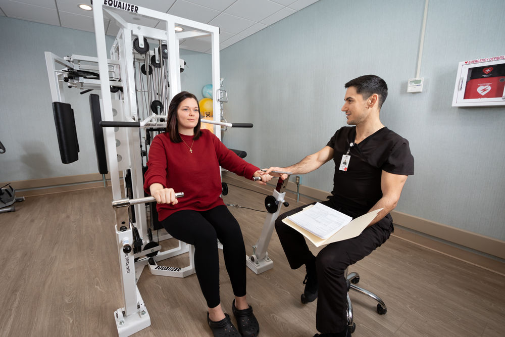 Physical Therapist assists woman on therapy machine.