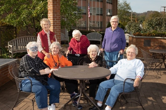 Elderly Welty residents lounging outside around a table and chairs.