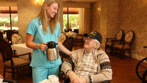 Nurse offering to pour an elderly man a cup of coffee while he is seated at a table.