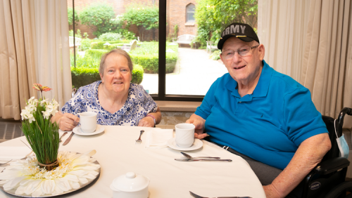 Army Veteran and lady enjoy coffee at dining table.