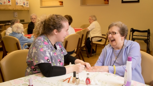 A nurse gives an elderly woman a manicure in an assisted living facility.