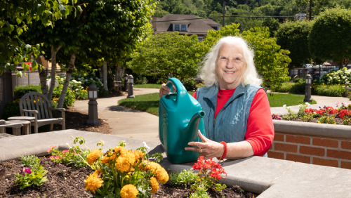 Smiling Welty resident waters garden flowers